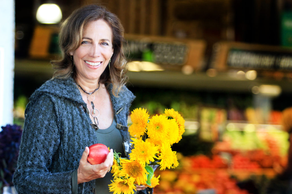 Beth Greer at the market holding an organic apple and colorful flowers