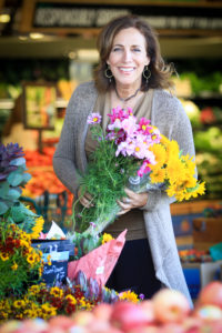 Beth Greer holding flowers at the market